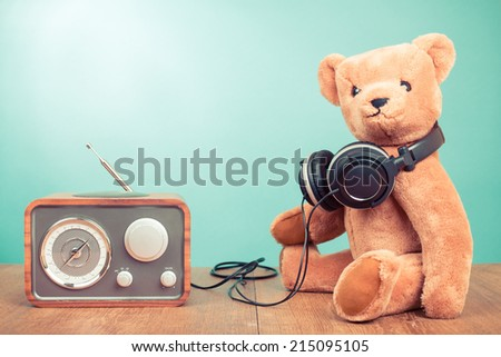 Retro toy Teddy Bear and radio receiver front mint green background - stock photo