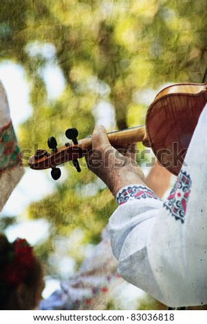 retro traditional festival picture with close-up man play on violin