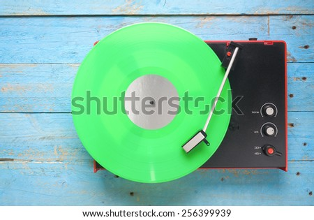 Retro turntable with green vinyl record, free copy space - stock photo