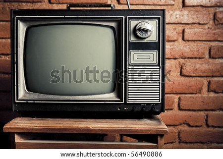 retro tv turned of against brick wall - stock photo