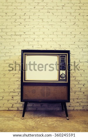Retro tv with brick wall background - stock photo