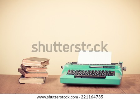 Retro typewriter and old vintage books on wooden table near empty wall background - stock photo
