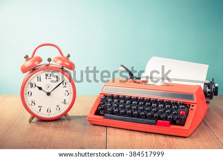 Retro typewriter, old alarm clock on table front mint green background. Vintage style filtered photo