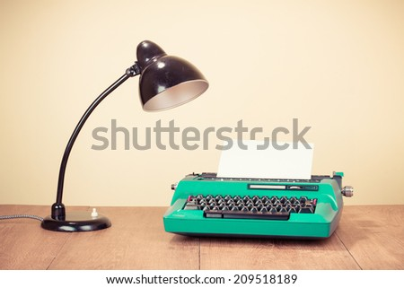 Retro typewriter with paper and old desk lamp on table - stock photo