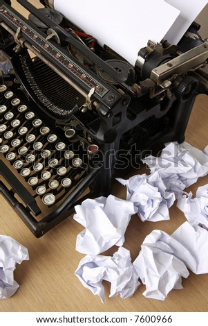 Retro typewriter with paper scattered all around - conceptual image for creative block - stock photo