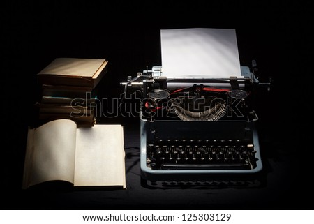 retro typewriter with stack of book and one opened book black background - stock photo