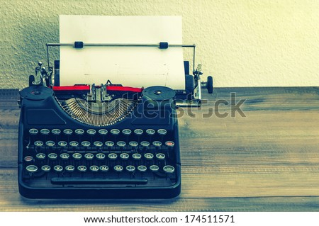 retro typewriter with white paper page on wooden table. vintage style toned picture - stock photo