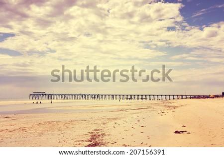 Retro Vintage instant filter wide open beach with beautiful cloud sky and jetty pier in background. - stock photo