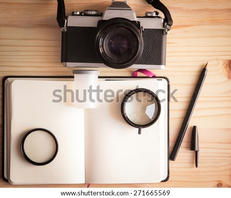 Retro vintage old photo camera with roll, lenses, notebook and pen on a wooden table - stock photo