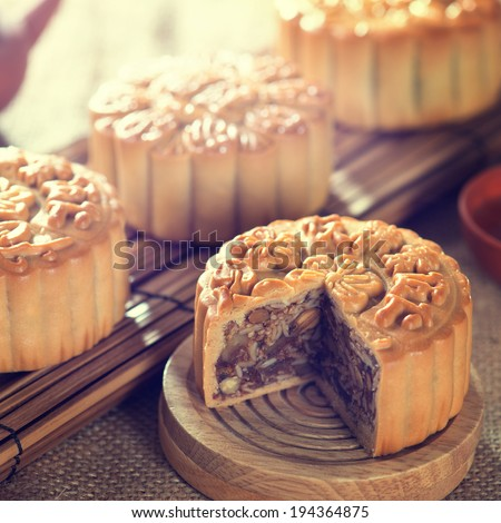 Retro vintage style Chinese mid autumn festival foods. Traditional mooncakes on table setting with teacup. The Chinese words on the mooncakes means assorted fruits nuts, not a logo or trademark. - stock photo