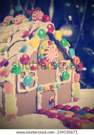 Retro vintage style Christmas gingerbread house made with sugar and candy sweets, in front of bokeh lights from Christmas tree. - stock photo