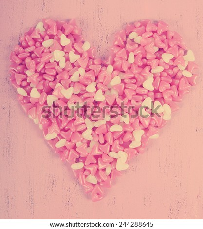 Retro vintage style Happy Valentines Day pink and white heart shape jelly candy on pink wood background. - stock photo