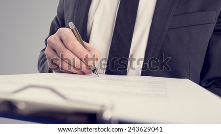 Retro vintage style image of a businessman signing a contract or document on a map. - stock photo