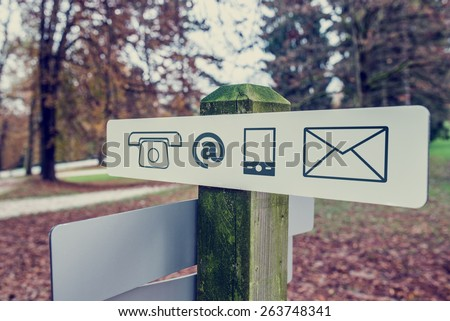 Retro vintage style image of a contact signboard with icons for telephone, email, mail and mobile outdoors in an autumn park. - stock photo