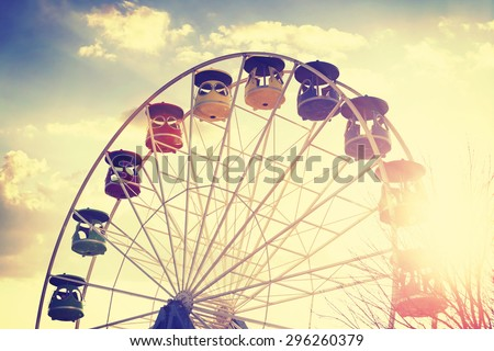 Retro vintage stylized picture of ferris wheel at sunset. - stock photo