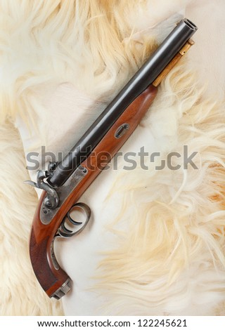 Retro wallpaper with british colonial pistol from the early 19th century. This gun's use as the last line of defense against an attacking tiger and other dangerous animal. - stock photo