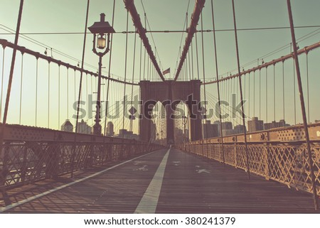 Retro Washed Out Color View of Historic Brooklyn Bridge with Arches and Cable Supports, Deserted Pedestrian Path with Old Fashioned Lamp in Warm Late Day Sun, New York City, New York, USA - stock photo