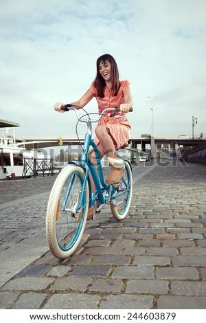 Retro woman enjoying day on bicycle - stock photo