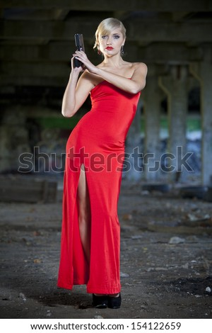 retro woman holding a gun in old fabric ruins - stock photo