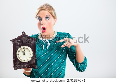 Retro woman is holding clock and showing that time is running out very fast.Time - stock photo