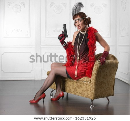 Retro Woman Portrait. Beautiful Woman armed with gun - stock photo