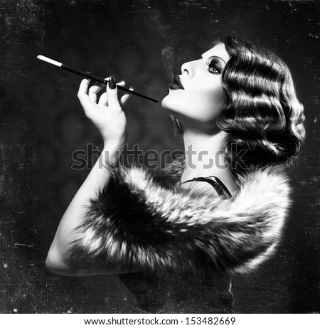 Retro Woman Portrait. Beautiful Woman with Mouthpiece. Cigarette. Smoking Lady. Vintage Styled Black and White Photo. Old Fashioned Makeup and Finger Wave Hairstyle. 20's or 30's style.  - stock photo