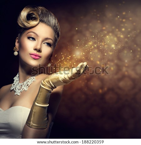 Retro Woman with magic in her hand. Beauty Fashion Vintage Style Lady with Beautiful Luxury Hairstyle, makeup, accessories. Golden Silk Gloves and dress - stock photo