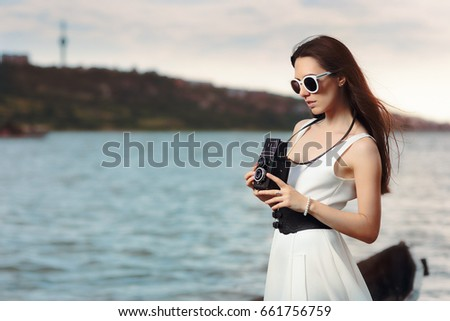 Retro Woman with Vintage Photo Camera on a Beach  - Beautiful girl in a white dress on the seashore near a boat