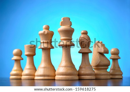 Retro wooden chess pieces standing in a line on a reflective wooden surface against a blue background with central highlight - stock photo