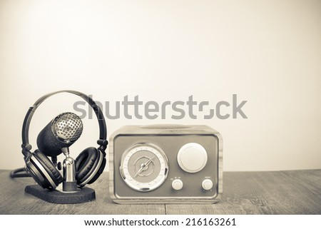 Retro wooden radio, microphone and headphones on table.  Vintage old style sepia photography - stock photo
