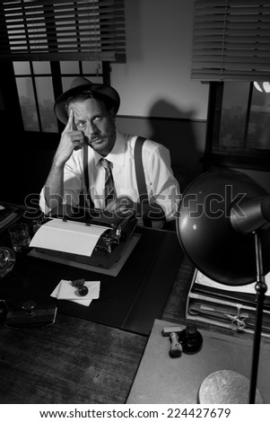 Retro writer working at desk with a typewriter looking for inspiration.