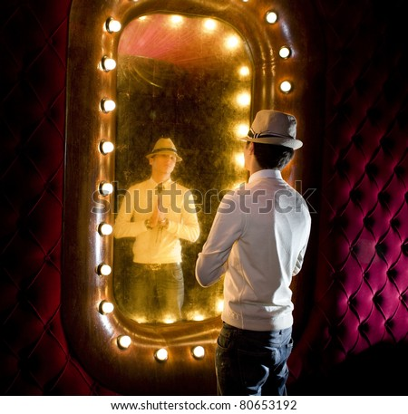 retro young man looks at himself in mirror - stock photo