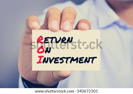 RETURN ON INVESTMENT (or ROI) message on the card held by a man hand, vintage tone - stock photo