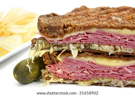 Reuben sandwich, with pastrami, sauerkraut, melting Swiss cheese on dark rye bread.  With dill pickle and potato crisps. - stock photo
