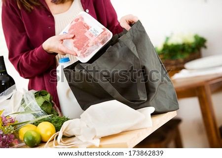 Reusable Bags: Unpacking Meat From Fabric Bags - stock photo