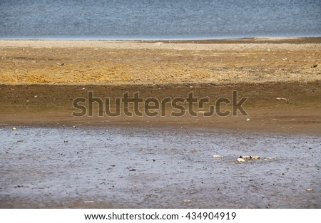 reveled bottom of a drying dam with colorful soil - stock photo