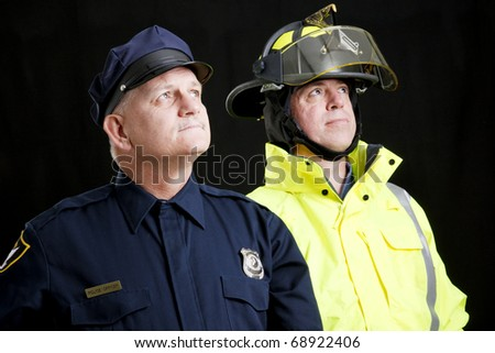 Reverent looking policeman and fireman photographed in front of a black background. - stock photo