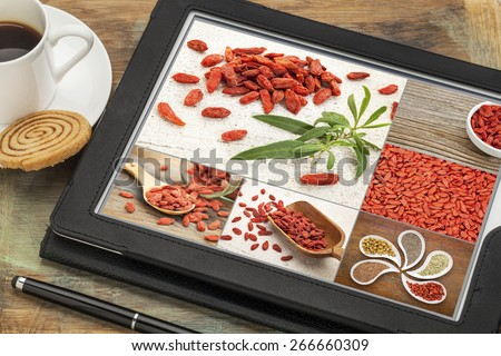 Reviewing and editing pictures of goji berries on a digital tablet. All screen pictures copyright by the photographer. - stock photo