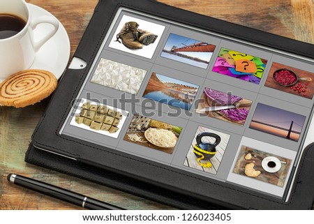 reviewing image library (grid of thumbnails) on a digital tablet computer, table with a cup of coffee; all displayed pictures copyright by the photographer - stock photo