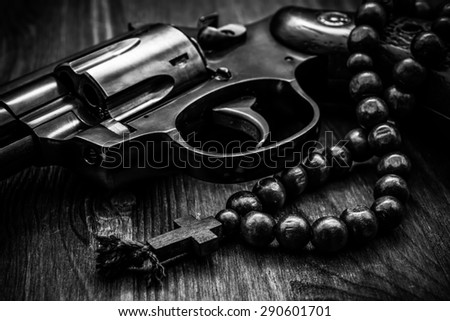Revolver and a rosary on the wooden table. Focus on the rosary. Close up view, in black and white tones - stock photo