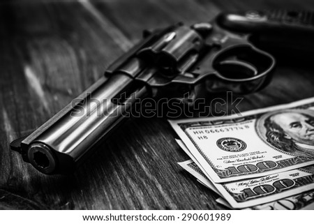 Revolver and money on the wooden table. Close up view, focus on the dollars, in black and white tones