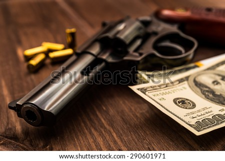 Revolver and pack of dollars with cartridges on the wooden table. Close up view, focus on the dollars