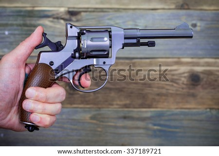 revolver gun in a human hand on a background of old boards - stock photo