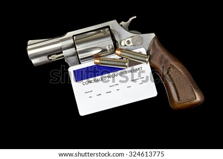 Revolver Gun with Concealed Weapon Permit Isolated on Black Background - stock photo