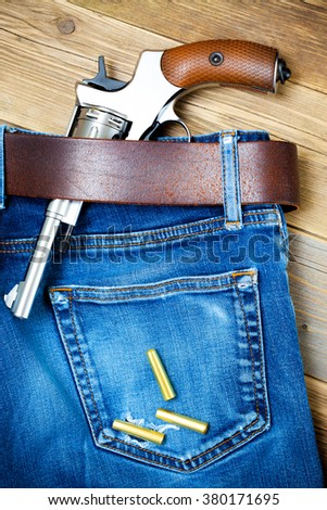 revolver in his belt of old blue jeans and a few yellow cartridges - stock photo