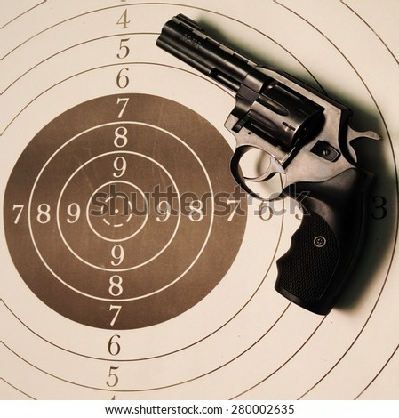 revolver. pistol lies on a target for shooting range - stock photo