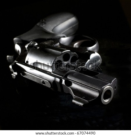 revolver that is starkly lit on a black background - stock photo