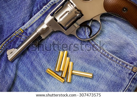 revolver with ammunition on blue jeans background, close-up, part of - stock photo