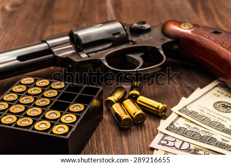 Revolver with cartridges and money on the wooden table - stock photo