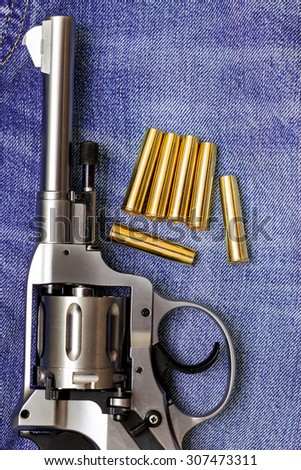 revolver with cartridges on blue jeans background, close up, part of - stock photo